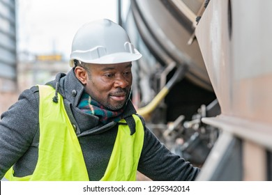 African American railroad engineer wearing safety equipment (helmet and jacket) checking gear train
