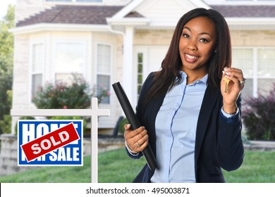 African American real estate agent holding keys in front of sold house