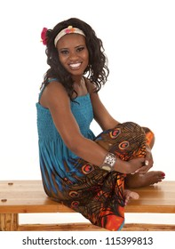 An African American relaxing on a bench in her colorful dress.