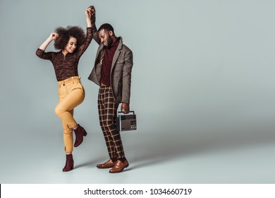 african american retro styled couple dancing with vintage radio on grey