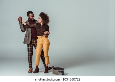 african american retro styled couple dancing on grey, vintage radio on floor