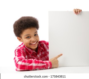African American school boy, teenager smiling and pointing at empty white blank board, education and school concept. Isolated, over white background, with copy space.