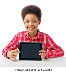 African American school boy, teenager smiling and pointing at empty black blank tablette, education and school concept. Isolated, over white background, with copy space.