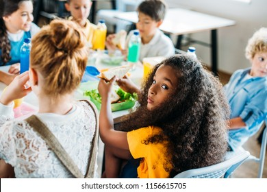 african american schoolgirl taking lunch at school cafeteria with her classmates and looking at camera