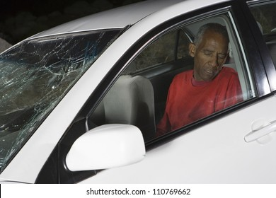 An African American senior man in car sitting unconsciously