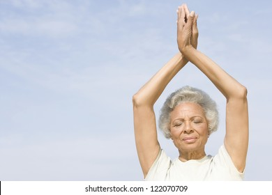 An African American senior woman practicing yoga against sky