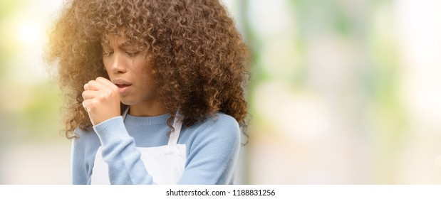 African american shop owner woman wearing an apron sick and coughing, suffering asthma or bronchitis, medicine concept