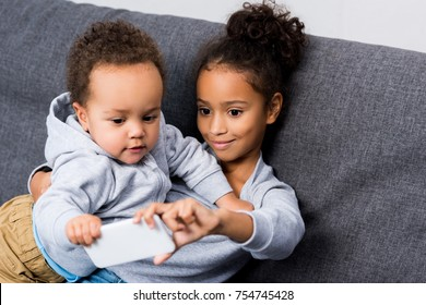 african american sister taking selfie with her little brother at home