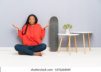 African American skater teenager girl with braided hair sitting on the floor having doubts with confuse face expression