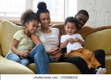 African american smiling family with two children having good time using smartphone. Young happy diverse husband and wife with cute daughter and son using applications in mobile phone.