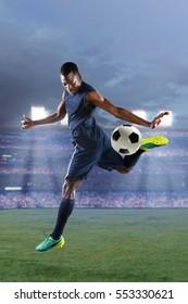 African American soccer player kicking ball with heel inside stadium