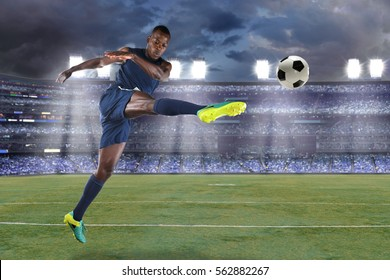 African American soccer player kicking ball inside large stadium
