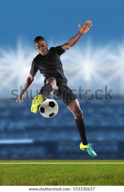 African American soccer player kicking ball inside stadium