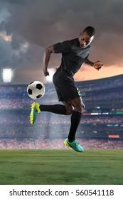 African American soccer player performing back kick inside stadium