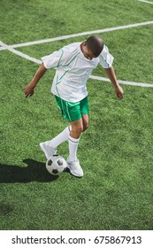 african american soccer player training with ball on soccer pitch