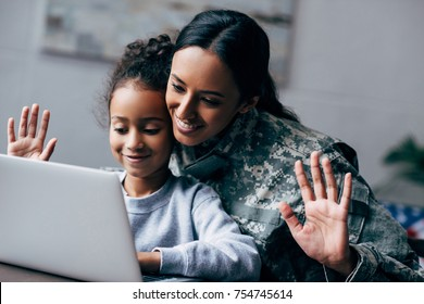 african american soldier in military uniform making video call on laptop with daughter at home
