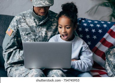 african american soldier in military uniform and child using laptop