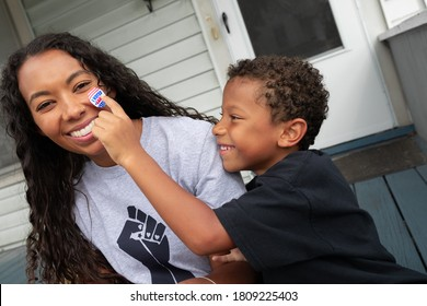 African American son placing I Voted Early Sticker face of happy mother wearing a social justice t-shirt
