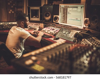 African american sound engineer working at mixing panel in boutique recording studio.
