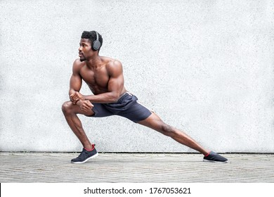 african american sports guy exercising fitness outdoors against wall, athletic man doing warm-up, healthy lifestyle concept, copy space