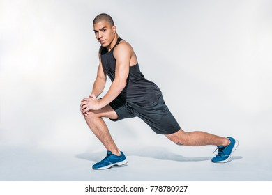 african american sportsman stretching legs and looking at camera