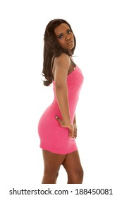 An African American standing in her pink dress with a serious expression on her face.