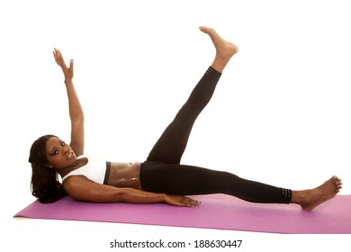 An African American stretching out her legs on her fitness mat.