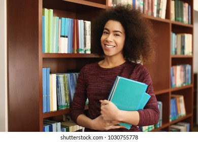 African American student with books in library