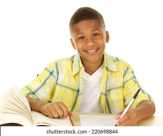African American student at desk writing and smiling at camera