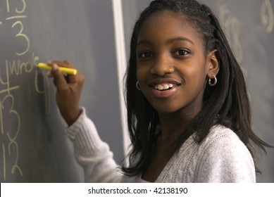 African American student doing math problems on the chalkboard