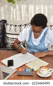 African American student makes translation exercises, rewrites sentences in notebook, drinks aromatic beverage, sits in front of laptop computer, writes story for famous magazine, notes some records