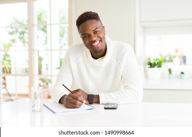 African american student man writing on a paper using a pencil with a happy face standing and smiling with a confident smile showing teeth
