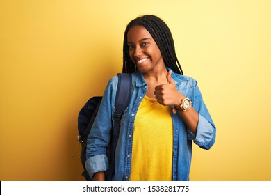 African american student woman wearing backpack standing over isolated yellow background doing happy thumbs up gesture with hand. Approving expression looking at the camera with showing success.