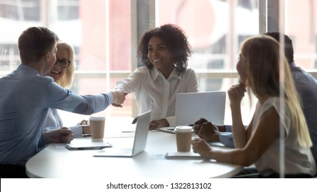 African American team leader shaking hand of businessman at company meeting in boardroom, greeting or getting acquainted, colleagues sitting at table together at business briefing or negotiations