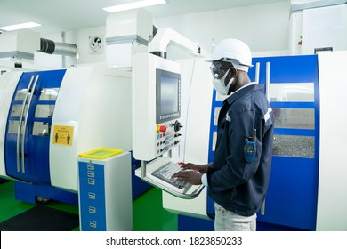 African American technician engineer operating CNC milling cutting machine in manufacturing workshop. Supervisor or Worker control computerized lathe machine in the metalwork factory on business day.