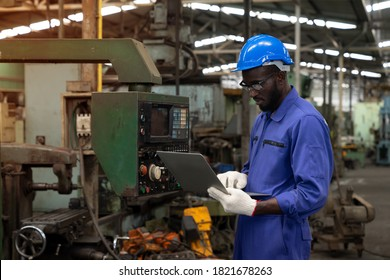 African american technician engineer use laptop to checking and control machines in the workplace on a business day. Industry worker working in the factory. Concept of Industrial manufacturing.