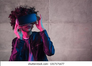 African American teen girl in trendy outfit wearing VR goggles and looking away while standing near concrete wall
