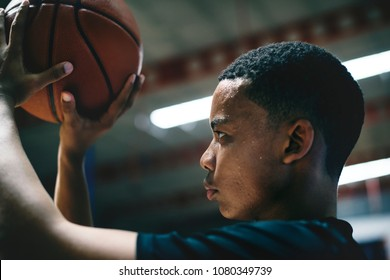 African American teenage boy concentrated on playing basketball