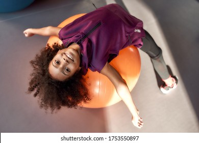African american teenage girl smiling at camera while working out with exercise ball in gym. Sport, healthy lifestyle, physical education concept. Horizontal shot