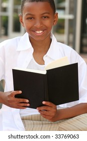 African American teenager boy reading a book on a bench outdoors, city street