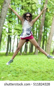 African American Teenager Girl with Hands Outstretched Jumping with Positive Expression in Green Forest Outdoors. Vertical Image Orientation