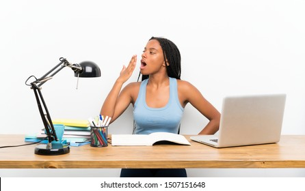 African American teenager student girl with long braided hair in her workplace yawning and covering wide open mouth with hand