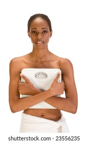 African American topless woman with her hips wrapped in bath towel covers her chest with weighscales confident in her success with weight control dieting strategy results