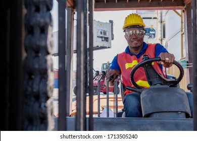 African American transportation business forklift driver with PPE Personnel Protective Equipment, safety vesy goggles and helmet is smiling happily and enjoy driving forklift at container yard of port