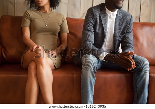 African american unhappy couple sitting on couch after quarrel fight thinking of break up or divorce, black upset man and woman not talking having conflict, bad relationships concept, close up view
