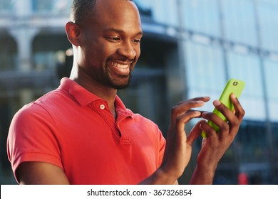 African American using smart phone in busy city to stay connected using social media