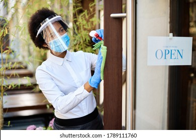 African American waitress with face mask and visor disinfecting front door while reopening cafe during coronavirus epidemic.