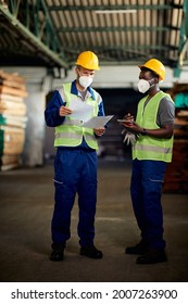 African American warehouse worker using digital tablet while his coworker is going through shipment list in distribution warehouse. They are wearing face mass due to COVID-19 pandemic.