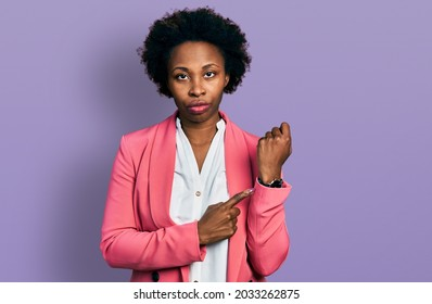 African american woman with afro hair wearing business jacket in hurry pointing to watch time, impatience, looking at the camera with relaxed expression