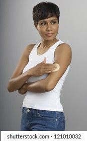 African American woman applying patch to her arm